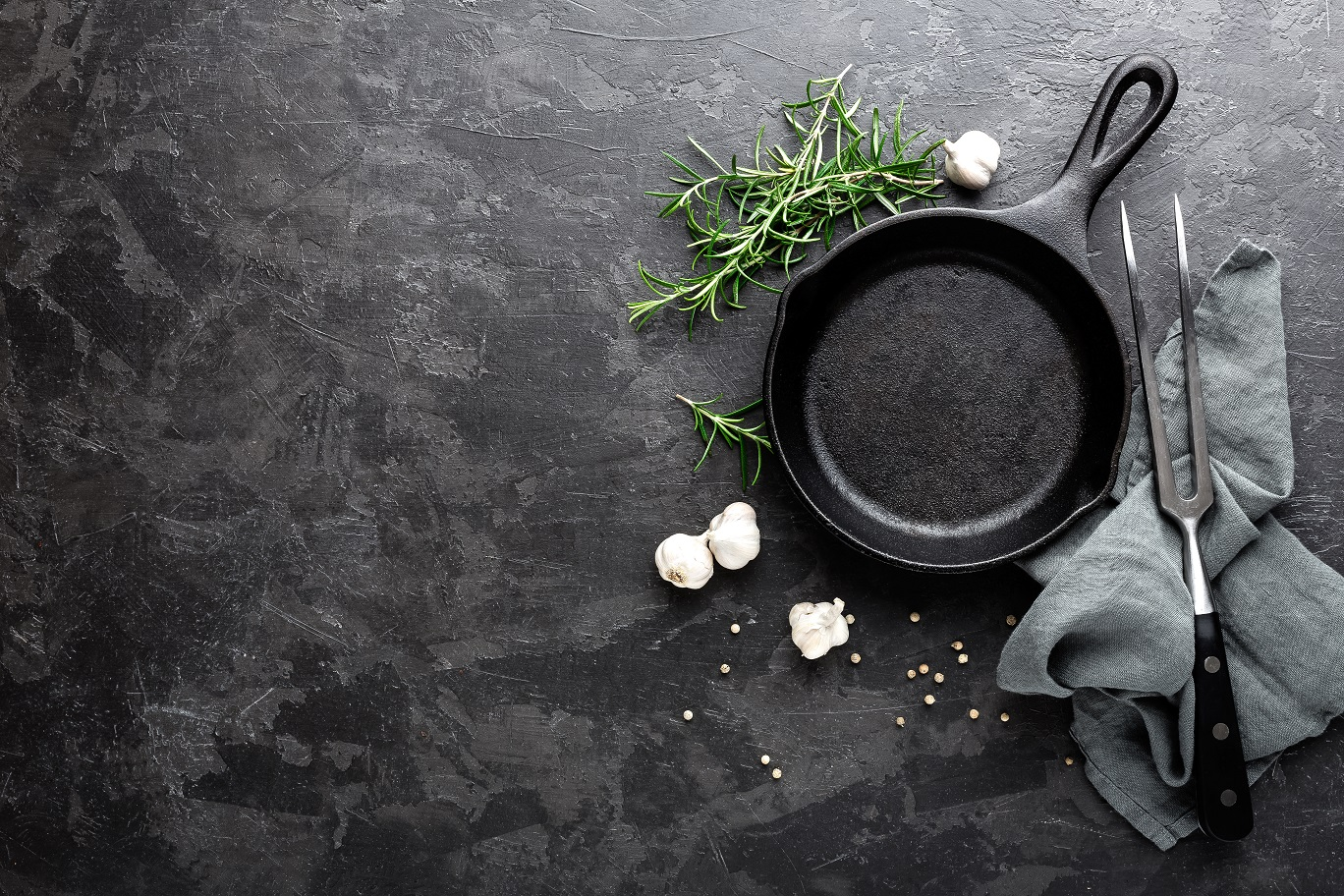 Black Cast iron skillet with garlic rosemary and a carving fork